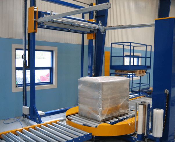 Conveyorized pallet wrapping line with top film sheet dispenser